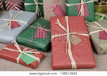 A pile of christmas presents on a burlap surface. The packages are wrapped in colorful tissue paper and plain brown paper.