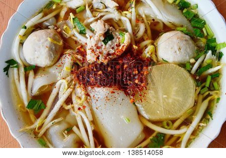 cayenne pepper on large noodle with pork ball in clear soup