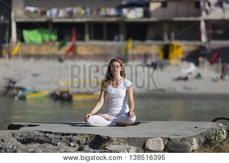Amazing beautiful young woman does yoga near ganges.