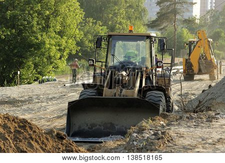 bulldozer, forklift and workers at the construction road junction in Moscow region