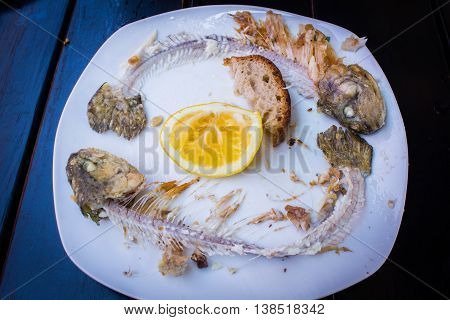 Scraps of fried fish on a white plate on stylish black table