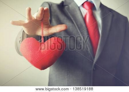 Businessman winning and controling customer's heart concept in Vintage tone