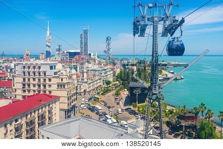 The cableway tower and the blue lift with the hotels and skyscrapers of Batumi on the backgound Georgia.