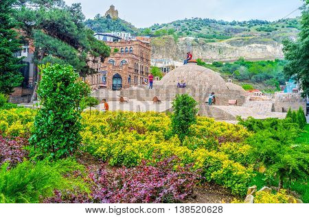 TBILISI GEORGIA - MAY 28 2016: The sulfur baths and garden of Abanotubani is the favorite place of children enjoying the games among the brick domes on May 28 in Tbilisi.