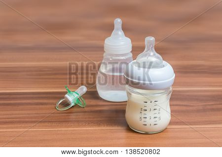 Bottles With Milk For Feeding Baby On Wooden Background.