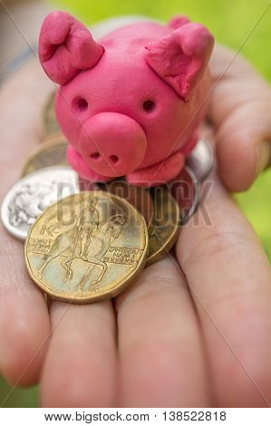 Hand is holding pink piggy - moneybox as symbol of savings