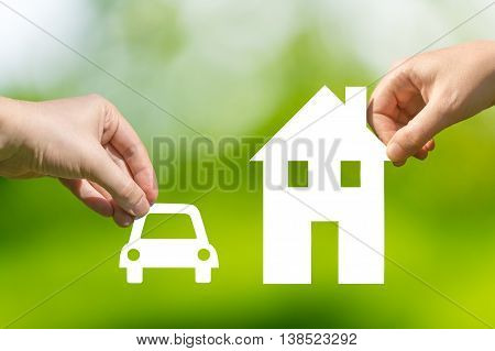 Hands Holding Cut Out Paper Car And House As Symbol Of Mortgage