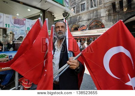 ISTANBUL - AUGUST 9: Unknown man sells turkish national flags in a street, August 9, 2013 in Istanbul, Turkey. Istanbul is the world's fifth-most-popular tourist destination.