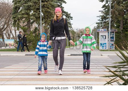Anapa Russia - March 9 2016: a young mother with two daughters cross the road at a pedestrian crossing