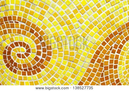 Yellow swirl pattern tiled bathroom wall. Mini square orange tiles background