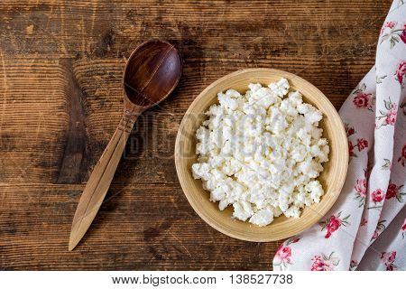 Cottage cheese (farmers cheese) in wooden bowl, wooden spoon, textile on rustic wooden table. Top view food. Healthy eating concept, country style