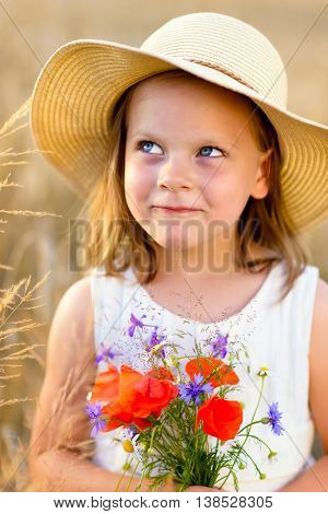 Little cheerful girl in a straw hat with wild flowers red poppy bouquet in the summer meadow - coquettish mischievous face