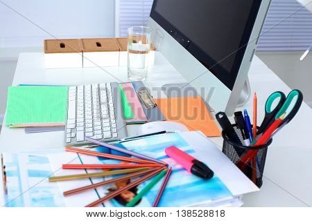 Designer working desk with a computer and paperwork.