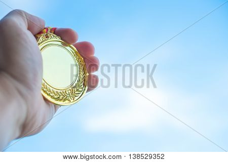 man holding a gold medal horizontal composition