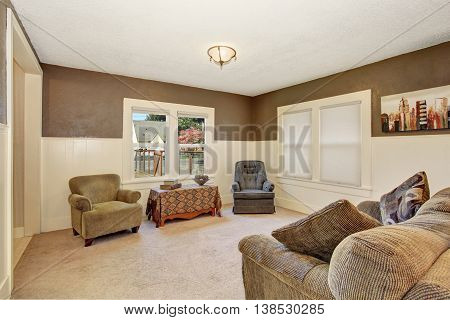 American Living Room Interior With Brown Walls And White Plank Panel Trim.