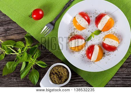 tomato. mozzarella caprese salad on white dish on table mat with bunch of basil and pesto sauce on background view from above