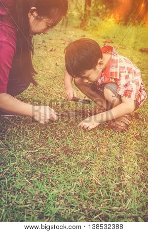 Asian mother and lovely son enjoying in nature. Young boy exploring nature at ground with magnifying glass. children playing outdoors with sunlight and happy family concept.