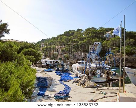 Cala Figuera Majorca Spain - June 22 2008: Fishermen boats in the harbor of Cala Figuera - blue fishing nets on ground.