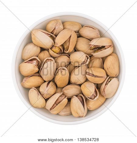 At the center of the frame white bowl with pistachio nuts on a white background. Salted roasted pistachios. Top view.