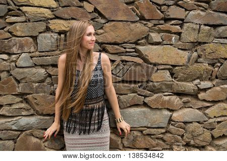 Modest young woman on the background of the old stone wall