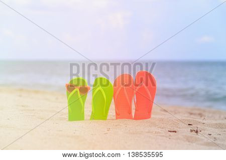Beach vacation concept- slippers and sunglasses at tropical beach