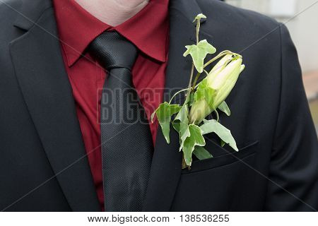 Groom's in a suit with a flower on Boutonniere
