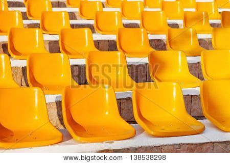 Stone steps with yellow plastic seats. Empty stools without people.