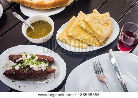 Georgian cuisine. Lula Kebab khachapuri next to the cutlery and lemonade