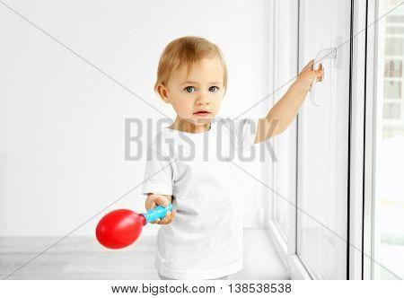 Little kid standing on a windowsill