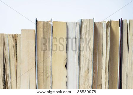 A stack of books in hard and soft cover. Book background