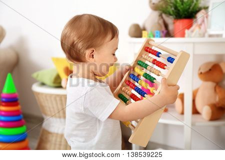 Cute baby girl playing with abacus in a white room  at home