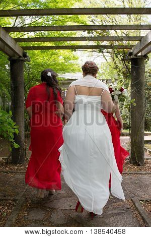Bridesmaids Walking And Looking After Bride Red And White Dress