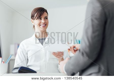Male customer at the pharmacy he is giving to the smiling pharmacist a prescription healthcare concept