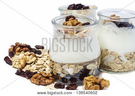 Healthy breakfast - yogurt with dried fruits honey and nuts and muesli served in glass jar isolated on white. Healthy lifestyle.