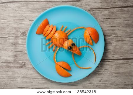 Crayfish made of orange on plate and board