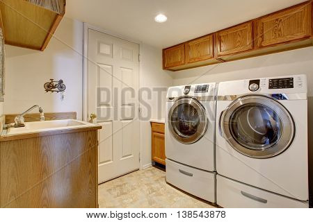 White Laundry Room Interior With Cabinets, Sink And Tile Floor.