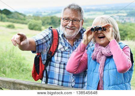 Senior Couple Hiking In Countryside Looking Through Binoculars
