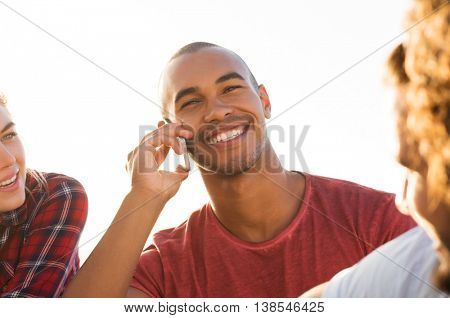 Cheerful young man with friends talking over phone at sunset. Happy smiling african guy in conversation through cellphone. Handsome black man with a big grin talking at telephone and looking away.