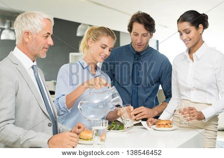Group of happy business team enjoying lunch in office. Happy young businesswoman pouring water in glass during lunch in office. Businesswomen and businessmen eating together at lunch.