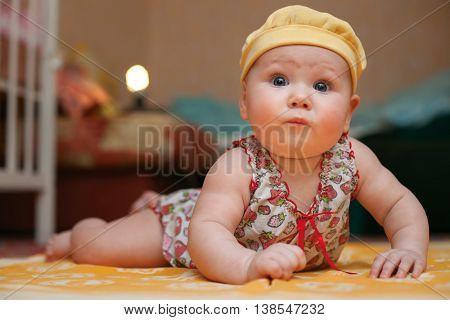 Little newborn girl in a cap in the room