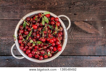 cherries in a colander on a wooden background.