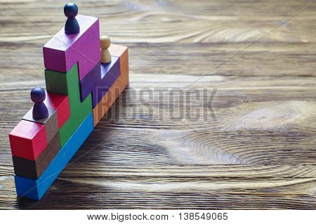 The concept of rewarding on a pedestal victories and achievements. Three wooden toy figures on the podium. Persons standing on the podium.