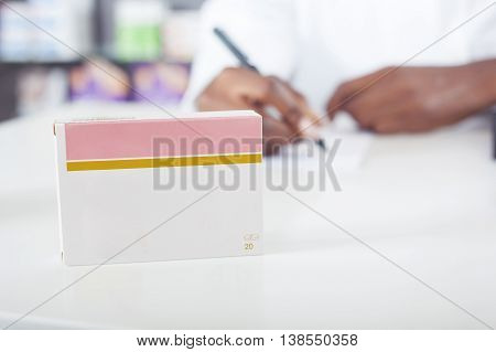 Black pharmacist or doctor writing with green tablet package with copy space