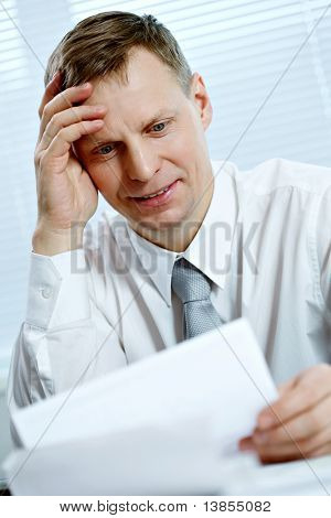 Portrait of a busy businessman looking at Portrait of a busy businessman looking at document cument