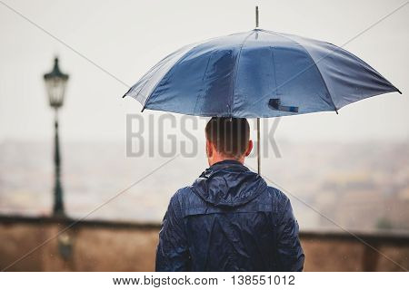 Rainy day. Young man is holding blue umbrella and walking in rain. Street of Prague Czech Republic. - selective focus on person