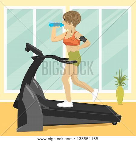 Young woman at gym doing exercise on the treadmill with smartphone armband drinking water