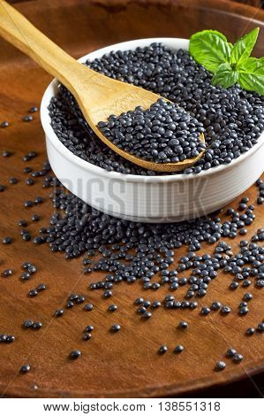 Round white bowl full of beluga lentils and basil leaves with wooden spoon on brown wooden background.