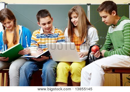 Portrait of clever students sitting in classroom and doing schoolwork
