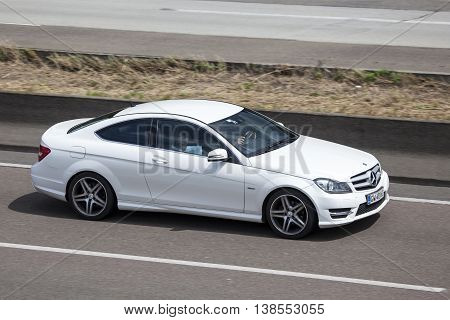 FRANKFURT GERMANY - JULY 12 2016: Mercedes Benz C-Class luxury coupe driving on the highway in Germany