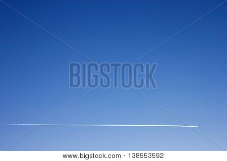 Minimalist photo of airplane contrail in blue sky